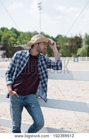 handsome cowboy in hat and checkered shirt looking away and leaning on fence at ranch