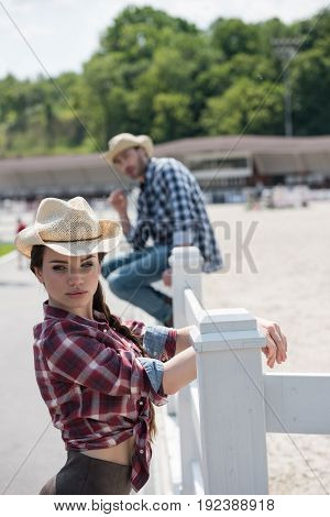 attractive woman in cowboy hat leaning no fence and looking away man sitting on fence behind