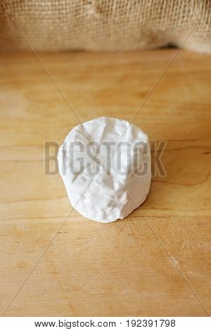 Buch cheese with white mold on a wooden Board