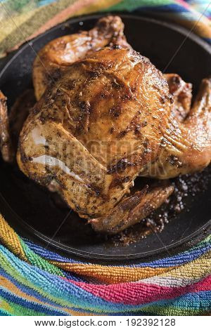 Fried fat chicken lays in a black frying pan on a multi-colored striped background a vertical frame.