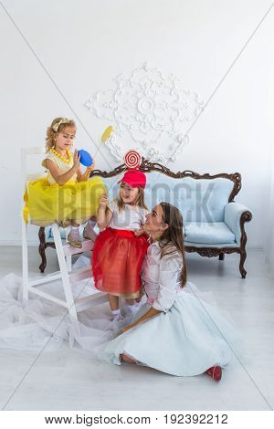 Mother and daughters with candy in the room
