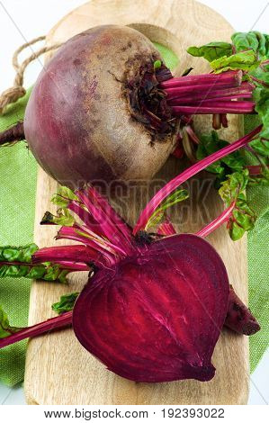 Fresh Raw Organic Beet Roots with Green Beet Tops Half and Full Body on Wooden Board and Napkin isolated on White background