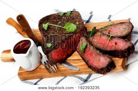 Sliced Delicious Roast Beef Medium Rare on Wooden Cutting Board with Tomato Sauce Fork and Table Knife closeup on Checkered Napkin