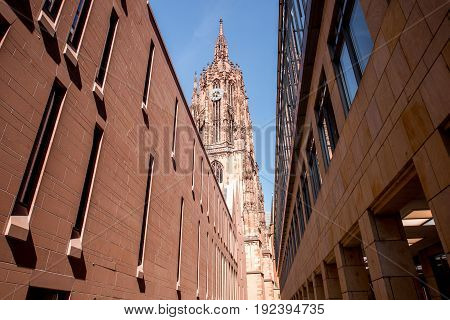 View on the tower of Frankfurt cathedral from Bendergasse street in the old town of Frankfurt city, Germany
