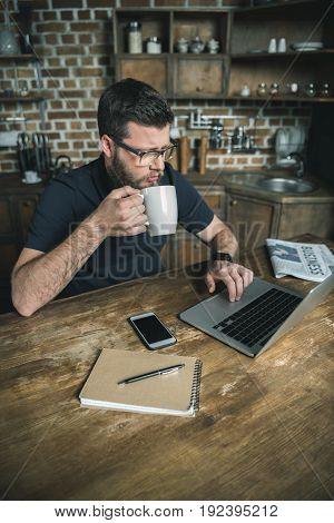 focused bearded freelancer drinking coffee during work on laptop in kitchen