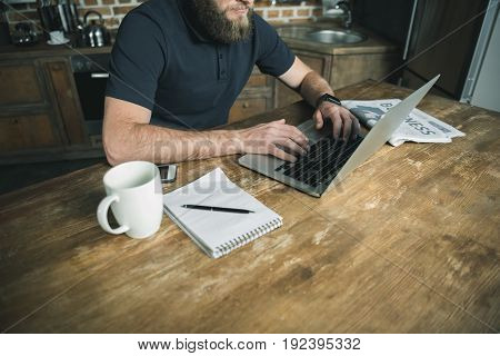 cropped view of bearded freelancer working with laptop in home office
