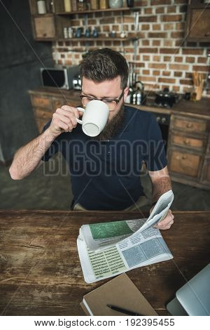 high angle view of man drinking coffee while reading newspaper at home