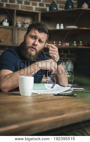 portrait of tired man with eyeglasses in hand looking aside while sitting at table