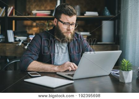 young caucasian man working on laptop while sitting at home
