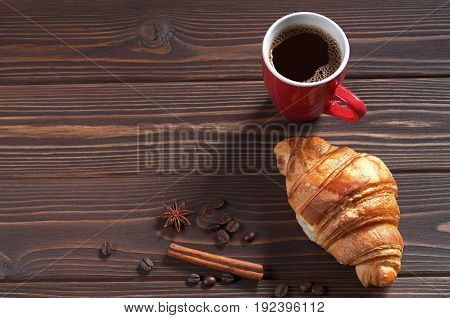 Cup of hot coffee and croissant for breakfast on dark wooden table. Space for text