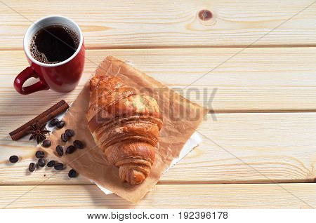 Cup of hot coffee and croissant on wooden background. Space for text