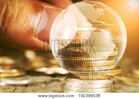 Double exposure of stacking coins and world ball saving business concept