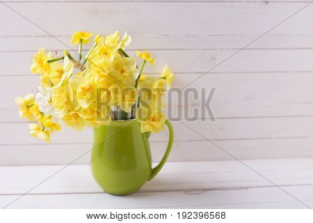 Yellow bright spring daffodils or narcissus flowers in pitcher on light wooden background. Selective focus. Place for text.