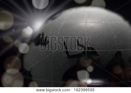 Close up of world ball with map during sunrise on dark background and bokeh