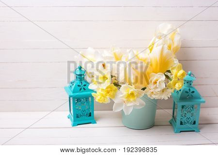 Yellow daffodils and tulips flowers in pot and blue decorative lanterns on white wooden background. Place for text. Selective focus.