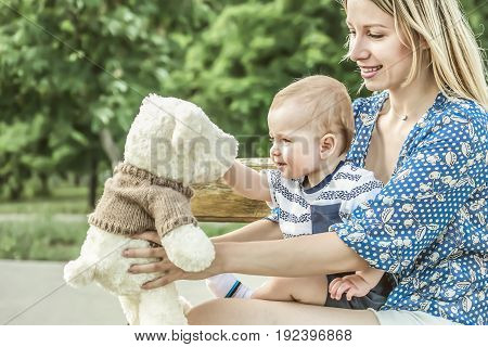 Pretty mather playing with baby boy outdoor on nature at sunny summer say