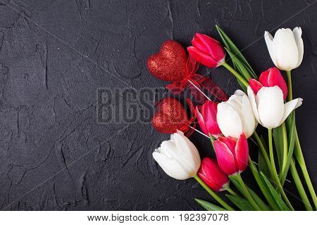 Red and white tulips flowers and decortive hearts on black textured background. Selective focus. Place for text.