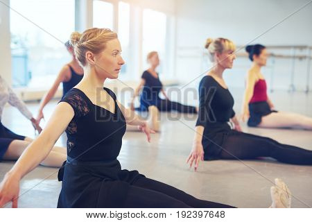 Group of adult ballerinas sitting on floor and doing fitness gymnastics in the class.