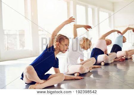 Little Girls Stretching On Floor In Ballet Class