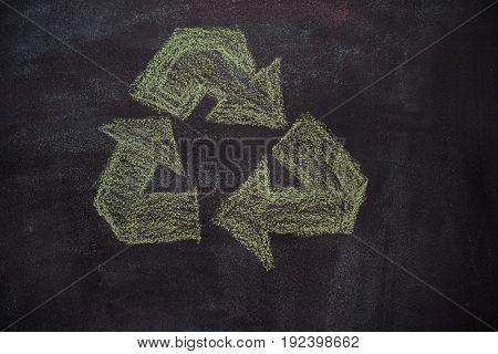 Green recycled symbol drawn with chalk on blackboard
