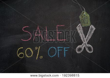 Sale 60% off. Sale and discount price sign with scissors cutting price tag drawn with chalk on blackboard