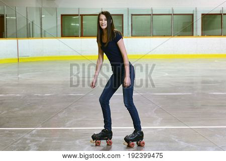 female teenager on quad roller skates in an arena