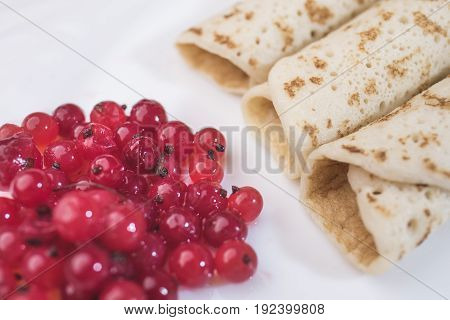 Bright red currant berries and three pancakes lie diagonally on a white background close-up