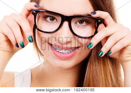 Vision and dentistry problems concept. Happy nerdy teenage wearing big eyeglasses showing her braces on teeth