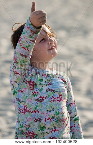 A Young girl on beach with kite smiling