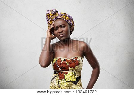 Mournful Black Woman With Deep-set Eyes And Full Lips Wearing Scarf And Dress Holding Hand On Temple