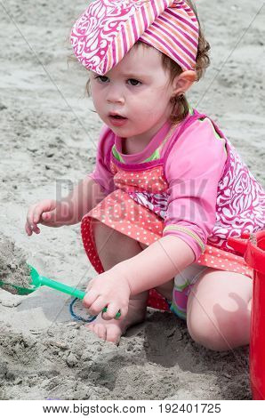A Young little girl playing with the sand and building sandcastle at the beach near the sea.