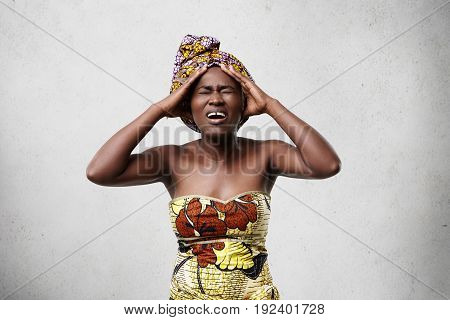 Portrait Of Stressed African Woman Wearing Colorful Clothing Holding Head Having Painful Look While