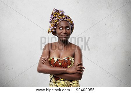 Frightened Dark-skinned Woman With Bugged Eyes And Full Lips Standing Crossed Hands Isolated Over Wh