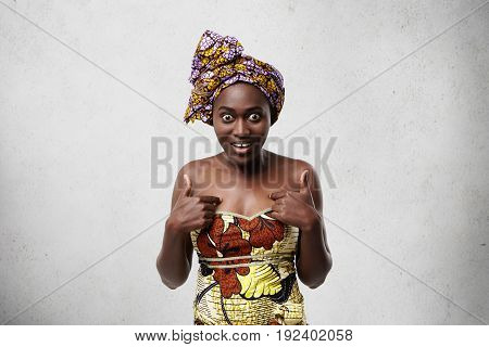 Middle-aged Black Woman In Traditional Clothes Looking At Camera With Widely Opened Eyes Having Surp