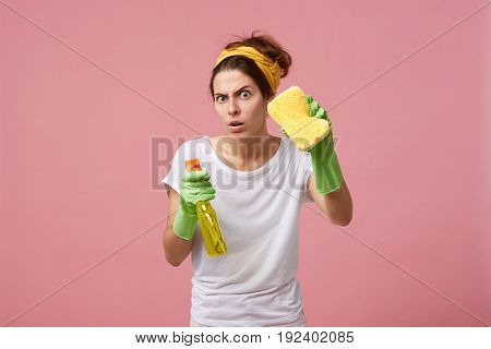 Emotional Cute Female Posing In Green Rubber Gloves, Equipped With Yellow Sponge And Spray Detergent