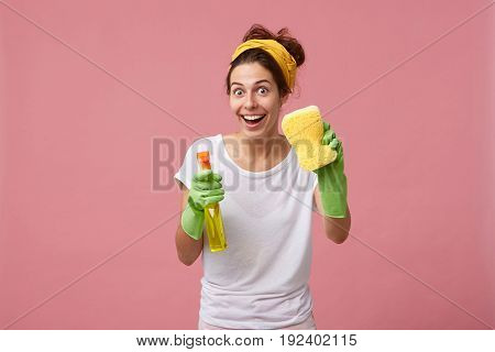 Happy Housewife Dressed In Casual Clothes Holding Sponge And Detergent Going To Clean House Having G