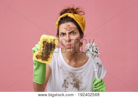 Portrait Of Aggravated Woman With Dirty Face Wearing Yellow Headband And White T-shirt Holding Bast