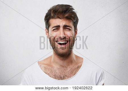 Positive Funny Bearded Man With Stylish Hairstyle Closing His Eyes While Smiling Sincerely. Cheerful