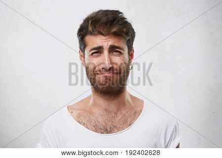 Discouraged Man With Hairdo And Beard Frowning His Face Being Sorry For What He Done. Grieved Man In