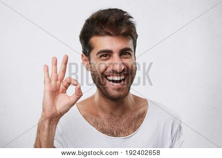 Portrait Of Glad Bearded Man With Stylish Hairstyle Showing Ok Sign Expressing His Agreement. Young