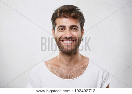 Stylish Bearded Man With Appealing Dark Eyes Smiling Into Camera Having Pleased Expression Being Gla