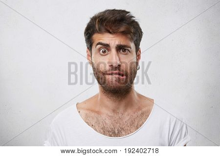 Nervous Doubtful Male With Stylish Hairstyle And Beard Frowning His Eyebrow, Biting Lips Having Puzz