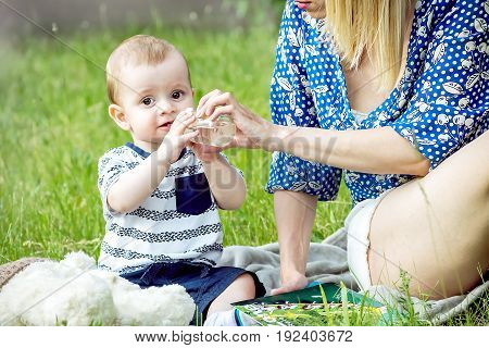 A pretty mather Giving water from a bottle with a pacifier to a baby boy sitting in a park on grass