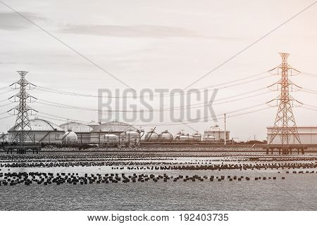 High voltage pole and storage marine tank farm on the sea port with vintage effect