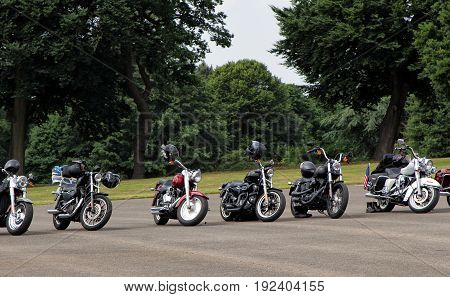 Sandhurst, Uk - June 18 2017: Row Of Motorcycles Left Parked In Front Of Parkland With Nobody Around
