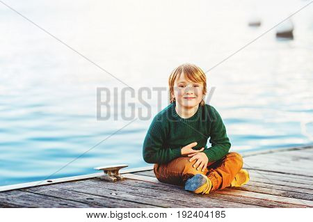 Outdoor portrait of adorable 5-6 year old boy resting by the lake wearing green pullover and yellow trousers