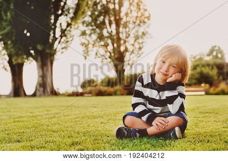 Outdoor portrait of adorable toddler boy sitting on grass at sunset