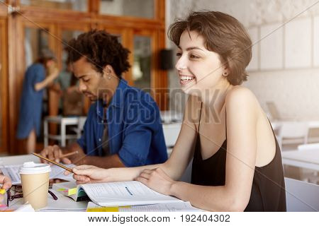 Smiling Young College Student Female With Trimmed Hair Wearing Casual Black T-shirt Sitting In Class