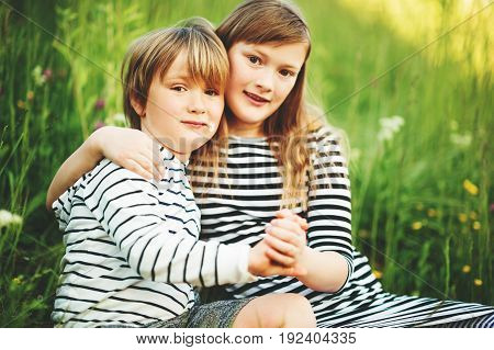 Outdoor portrait of two adorable kids playing together
