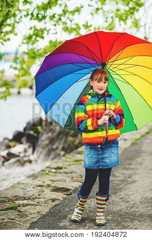 Outdoor portrait of pretty little kid girl with big colorful umbrella wearing rain jacket and boots weather concept fashion for kids